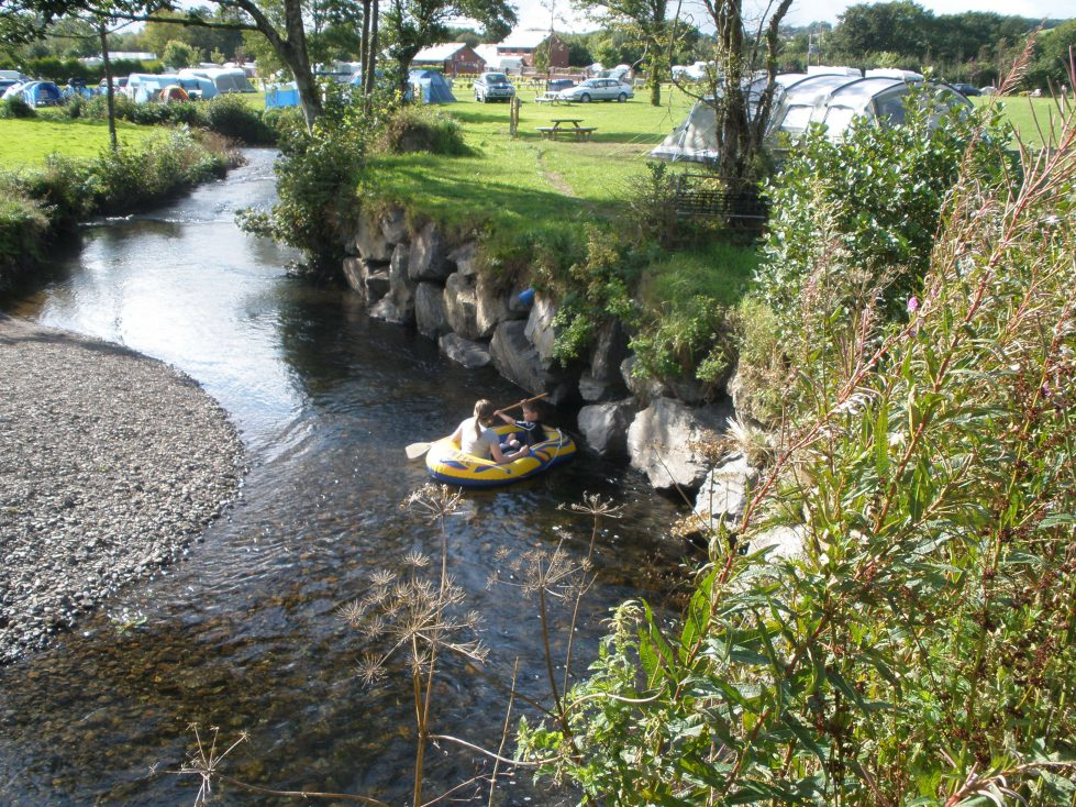Grass Pitch and stream at Riverside Camping & Caravan Park, South Molton